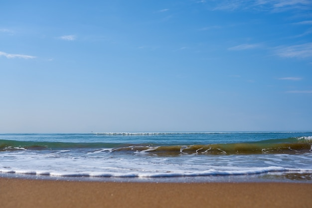 Ondas com espuma na praia arenosa do mar mediterrâneo indo além do horizonte