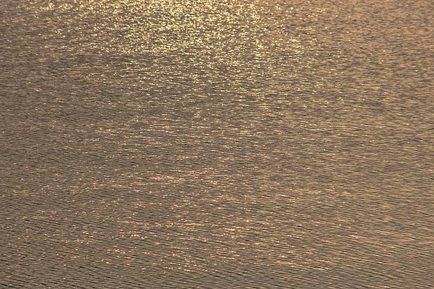 Ondas de água embaçada por vento e luz solar refletindo a superfície