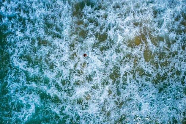 Ondas de fundo abstrato de água, o mar e a vista aérea de turistas de pequenas viagens do drone