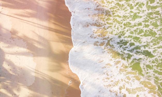 Ondas de praia de vista aérea do zangão ao pôr do sol.