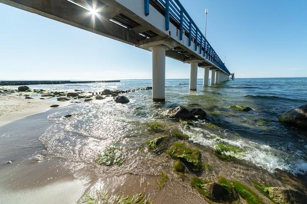 Ondas de surf com espuma do mar e algas marinhas na praia turística