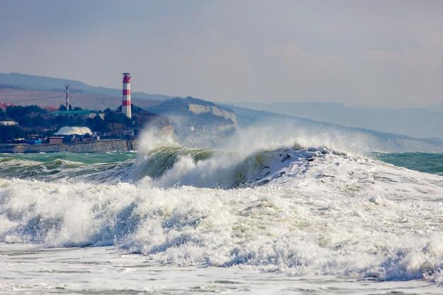 Ondas de tempestade bonitas e perigosas pelo farol gelendzhik. resort gelendzhik, cáucaso, costa rochosa íngreme.
