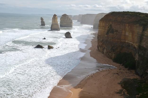 Ondas do mar atingindo a costa com pedras perto de falésias sob um céu nublado