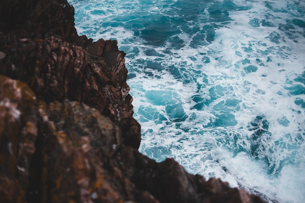 Ondas do mar azul espirrando nas rochas