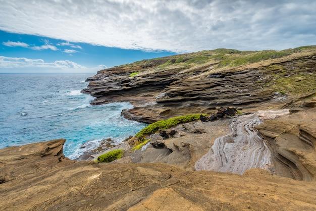 Ondas do mar batendo contra as formações rochosas de lava única do lanai lookout em oahu, havaí