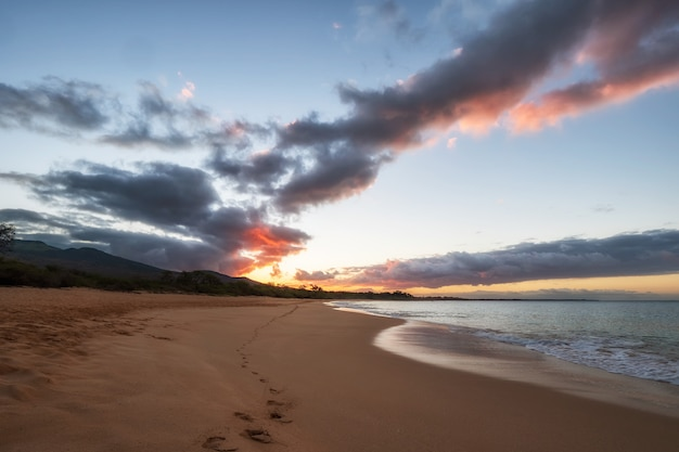 Ondas do mar batendo na praia durante o pôr do sol