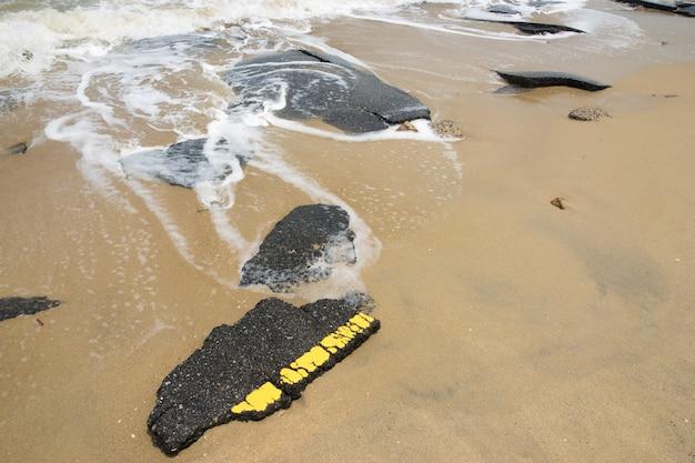 Ondas do mar causadas por uma forte tempestade atingem e destroem uma estrada de asfalto