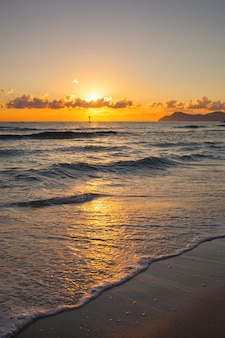 Ondas do mar e pôr do sol na praia mallorca can picafort