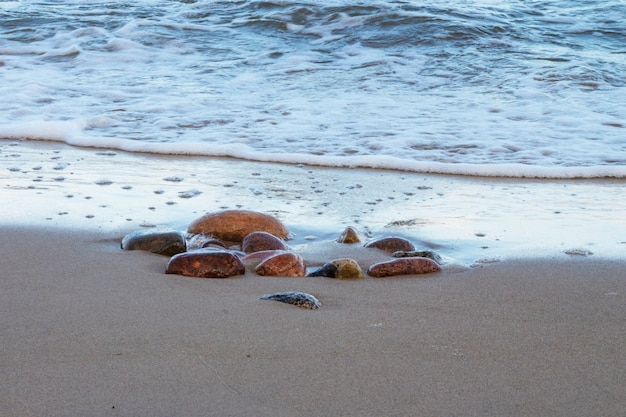 Ondas do mar e rochas na costa arenosa. férias no mar, maré alta