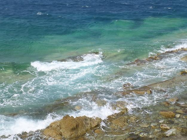 Ondas do mar egeu azul-turquesa batendo nas rochas na ilha de mykonos, grécia