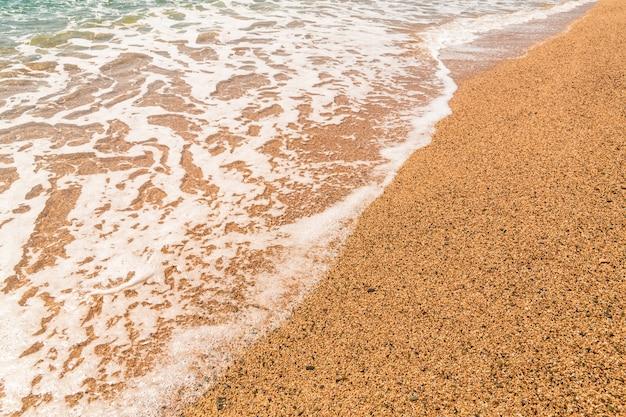 Ondas do mar na areia. praia de areia e as ondas do mar mediterrâneo na espanha