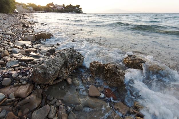 Ondas do mar na praia de pedra ao pôr do sol, zakynthos, grécia