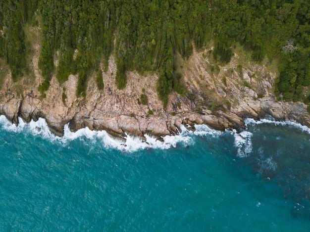 Ondas do mar, quebrando contra o penhasco, visto de cima