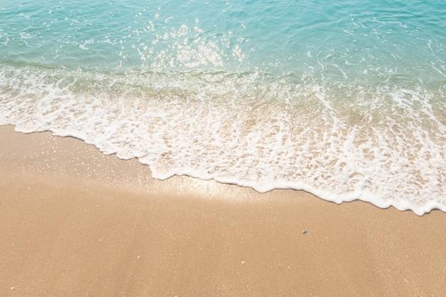 Ondas do oceano azul luz solar reflexo fundo da areia da praia