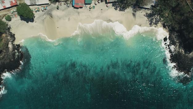 Ondas do oceano e paisagem de águas cristalinas de praias de areia branca na ilha tropical de bali na indonésia viajam