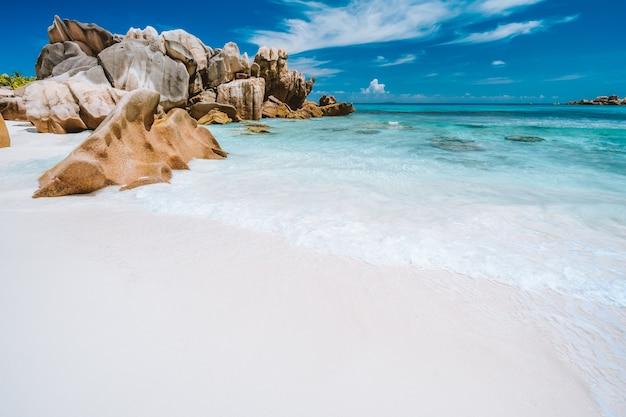 Ondas do oceano e rochas de granito, areia branca perfeita, água turquesa e céu azul