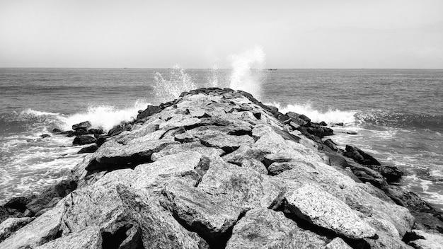 Ondas do oceano nas rochas - preto e branco