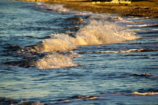 Ondas e respingos na praia ao nascer do sol