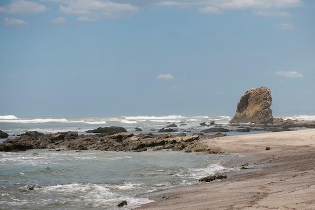 Ondas lambendo-se contra uma praia de areia com um afloramento de rochas e uma pilha no fundo