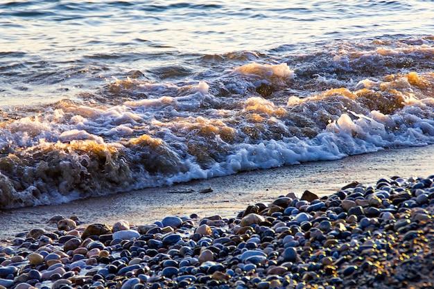 Ondas na praia de pedra sob a luz do pôr do sol