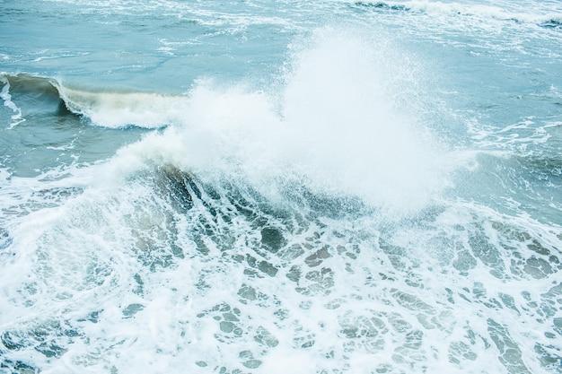 Ondas quebrando e pulverizando em alto mar e ventos fortes. ataque no mar no outono dia nublado chuvoso.