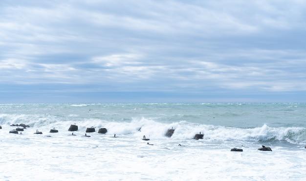 Ondas quebrando em quebra-mares de concreto marinho em águas rasas. proteção contra ondas viajantes, quebra-mar de concreto.