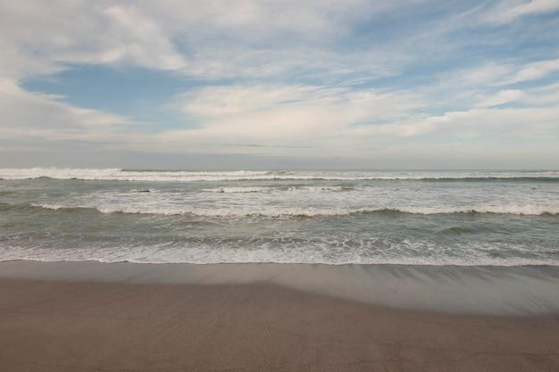 Ondas quebrando na praia sob um céu azul nublado
