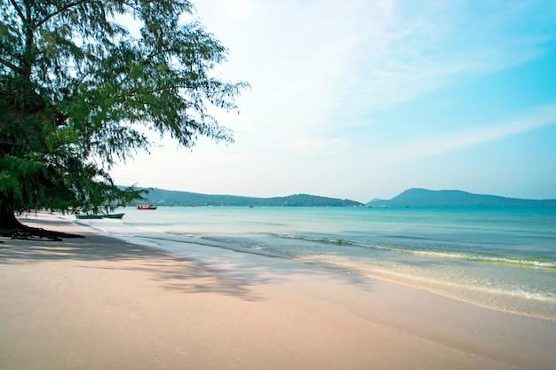 Ondas suaves do oceano em uma longa praia tropical de areia amarela com muitas pegadas na bela ilha de koh rong, camboja