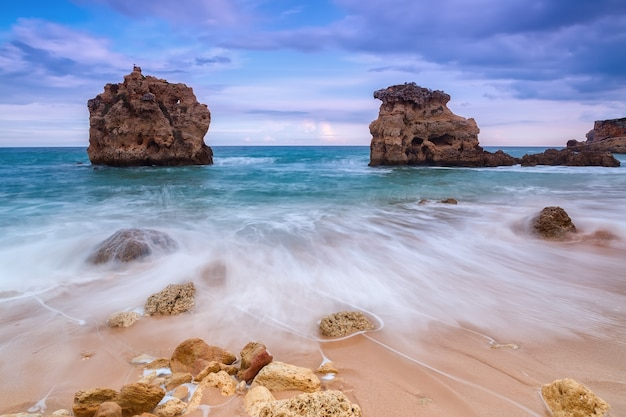 Ondas turvas fluem ao longo da costa rochosa. bela paisagem antes da tempestade.