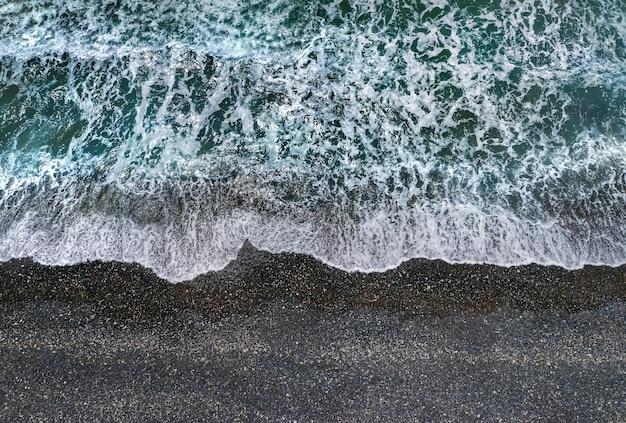 Ondas verdes tempestuosas com espuma branca do mar quebrando na praia de areia escura, vista diretamente de cima