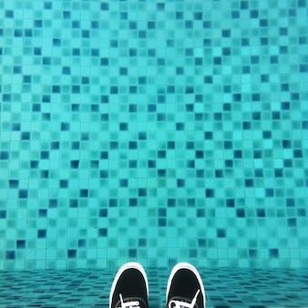 Onde estou, tênis pretos na piscina de ladrilhos de pixels.
