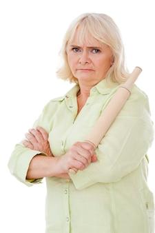 Onde você esteve? mulher sênior com raiva segurando o rolo de massa e olhando para a câmera em pé, isolado no fundo branco