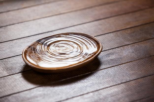 Ondinhas da água em uma tigela de madeira