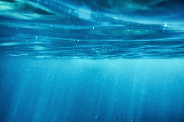 Ondulação da superfície do oceano azul subaquático com raio de sol no fundo do mar tropical