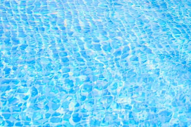 Ondulação de água azul na piscina com reflexo do sol