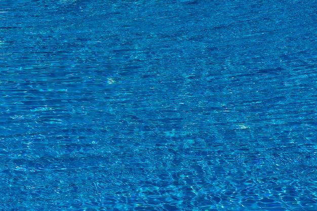 Ondulações da água no fundo da piscina de azulejos azuis. água azul turquesa da piscina. ondinhas iluminadas pelo sol. azulejos visíveis abaixo. vista do topo