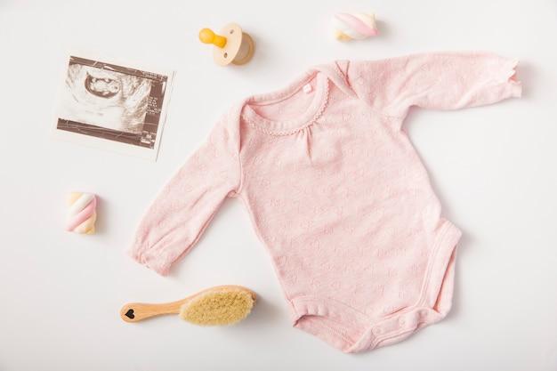 Onesie cor-de-rosa do bebê com retrato da ecografia; chupeta; marshmallow; escova no fundo branco