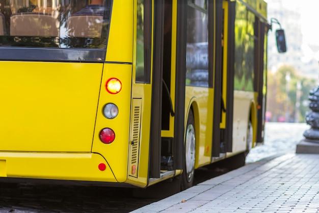 Ônibus da cidade amarelo moderno com portas abertas na rodoviária