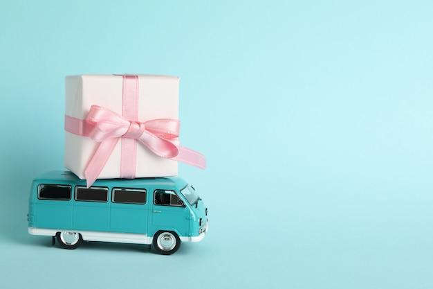 Ônibus de brinquedo com caixa de presente em fundo azul