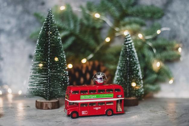 Ônibus de dois andares de brinquedo e pinheiro com luzes de natal
