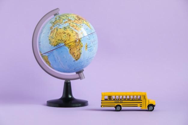 Ônibus escolar amarelo tradicional e globo terrestre em roxo