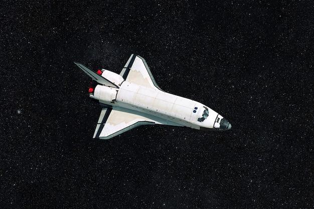 Ônibus espacial no espaço sideral em um fundo escuro e estrelado. nave espacial voa e explora o universo