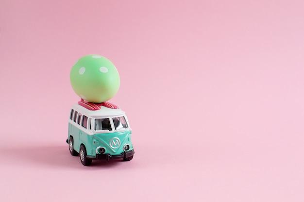 Ônibus hippie com ovos de páscoa coloridos no banner de carro pequeno em miniatura