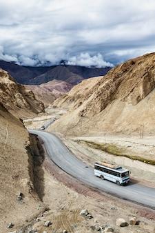 Ônibus indiano de passageiros na estrada no himalaia. ladakh, índia