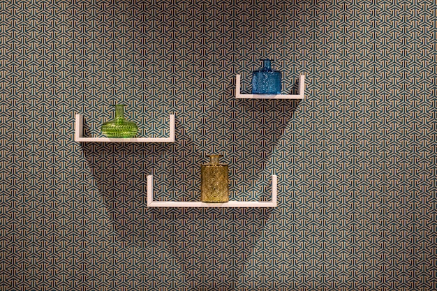 Onn três prateleiras brancas modernas bonitas abstraem a parede, com artigos decorativos, um vaso bonito.