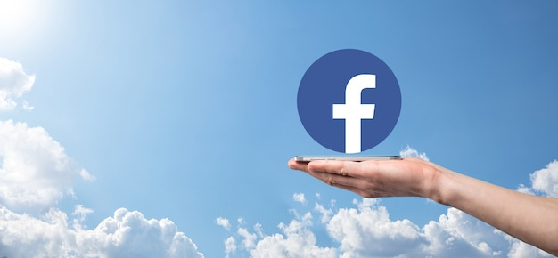 Onok, ucrânia - julho de 14,2021: empresário mantém, clica, ícone do facebook em suas mãos. rede social network.global e rede de conexão de dados do cliente.