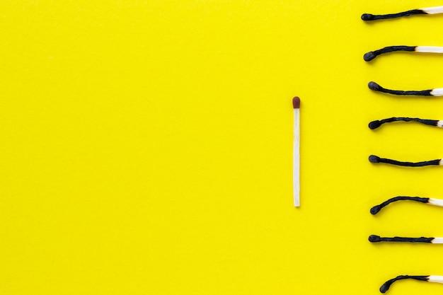Onr não utilizado e grupo de palitos de fósforo queimados em fundo amarelo