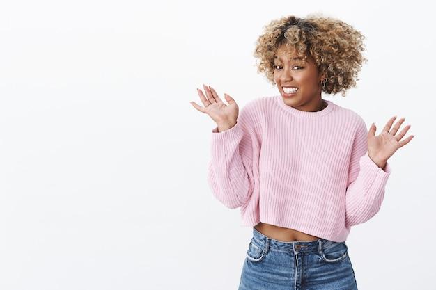 Opa, eu deixei cair. garota afro-americana fofa, tola e estranha, nervosa e desajeitada quebre coisa cara levantando as mãos em voz alta e cerrando os dentes preocupada em expressão de pesar parecendo estressada, se desculpando