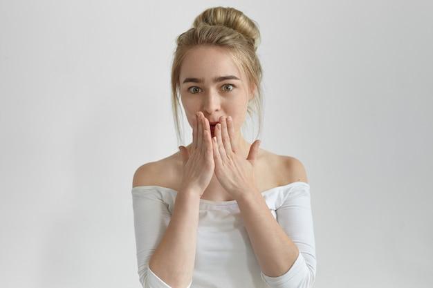 Opa. foto de uma linda jovem emocional com o coque ouvindo cobrindo a boca com as mãos, tentando não contar segredos, sendo surpreendida com notícias ou fofocas surpreendentes, olhando com olhar chocado