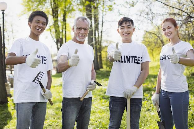 Opção de voluntariado ambiental. feliz quatro voluntários mostrando os polegares e segurando ferramentas de jardim